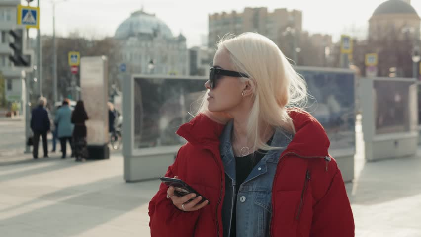 Young happy teenage girl using phone and having fun in spring park. Blonde happy model woman portrait student in down jacket and sunglasses on street smartphone. #1010564768
