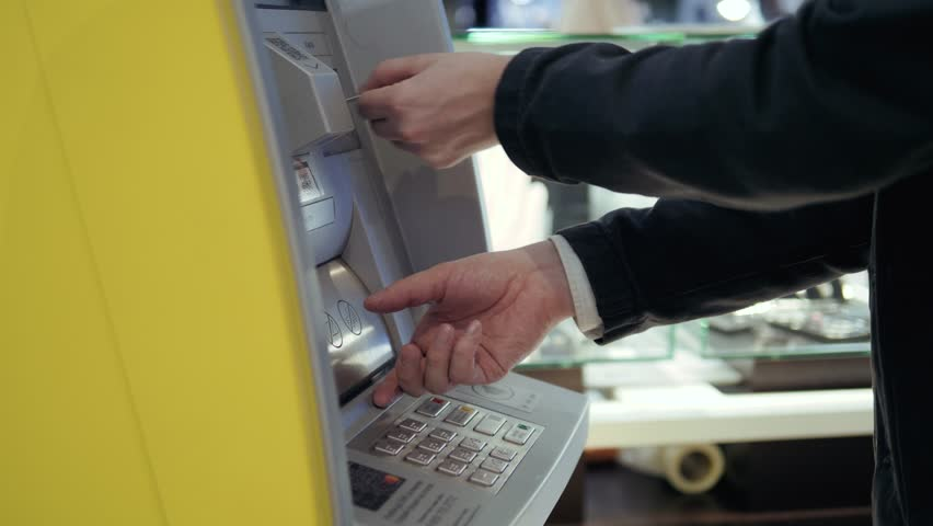Man using his credit card in an atm for cash withdrawal, pin code money shopping mall, during coronavirus quarantine