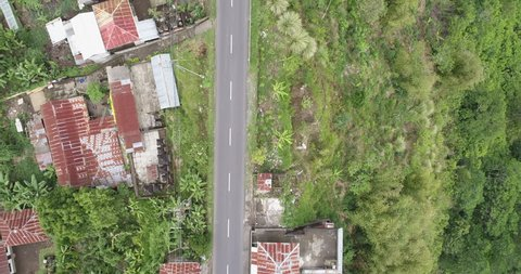 Flying over of Asian village and road. Aerial view of Bali - October 2017: Ubud, Bali, Indonesia