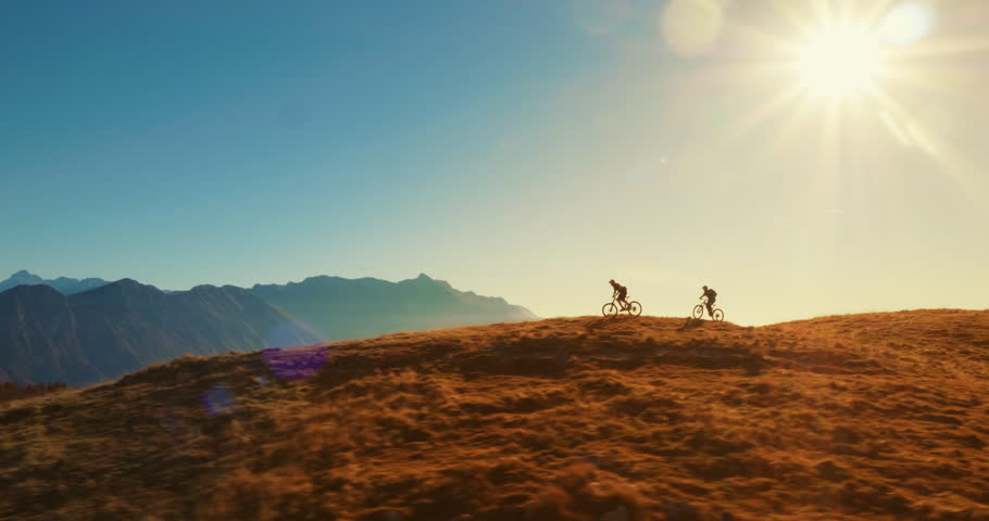 Aerial tracking of mountain bikers on cross-country cycling in amazing sunlight.
