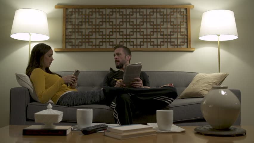 Couple lounging on sofa at home using mobile phone and doing crossword puzzle. | Shutterstock HD Video #1010578484