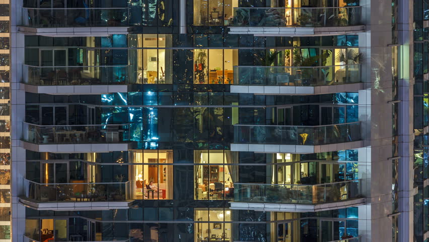 Scenic glowing windows of skyscrapers at evening timelapse. View of modern residential high-rise buildings in Dubai marina. People moving inside apartments. Aerial top view. Pan up | Shutterstock HD Video #1010579642
