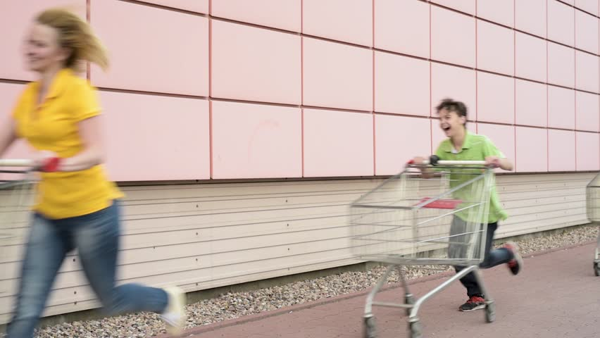 Happy family with shopping carts in a parking lot near a supermarket. People runing and engaged in purchases in shopping centre. Mom, Dad, Children having fun outdoors with shopping trolleys race. #1010581037