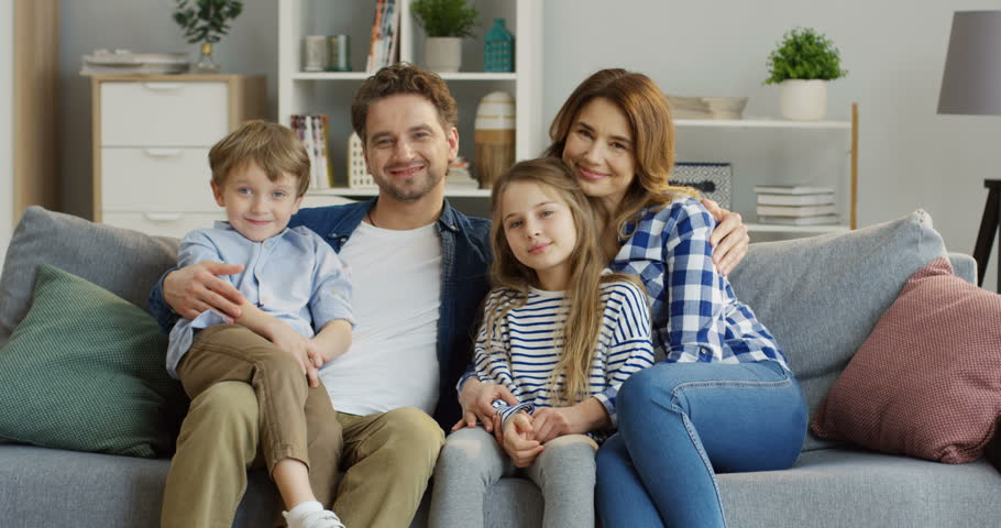 Good looking caucasian family of mother, father, son and daughter sitting on the sofa in the living room and smiling in front of the camera. Portrait shot. Indoors #1010582414