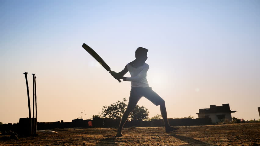 Slow motion shot of young village teenager playing bare feet in a open field hits the cricket ball and runs. a silhouette shot of young man playing cricket in a summer vacation