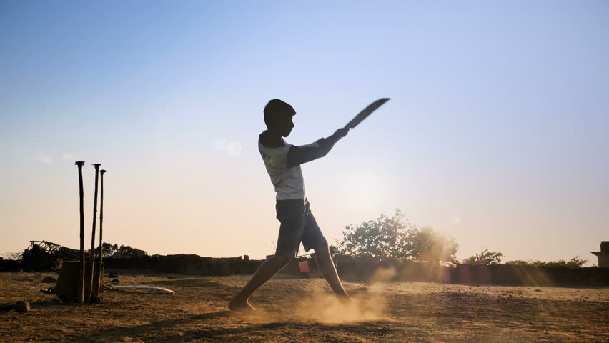 A young boy batting hits the cricket ball for a six in a open field in an Indian village. A slow motion shot of a teenager playing cricket against the sun strikes the cricket ball hard in rural India
