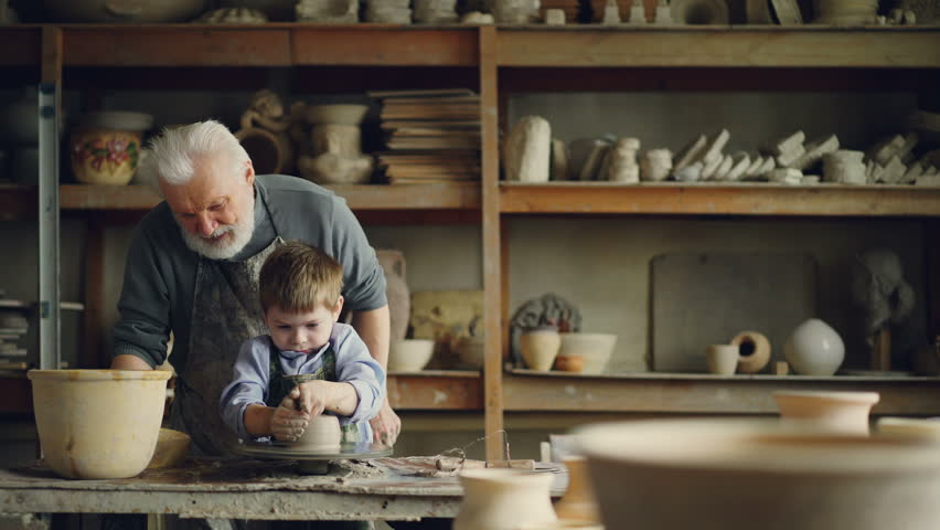 Caring grandfather experienced potter is teaching little boy how to work with clay on potter's wheel. Grandson is making mistake, patient grandpa is helping him.