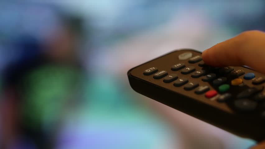 People hand using remote control with television programs closeup blur interior background | Shutterstock HD Video #1010640626
