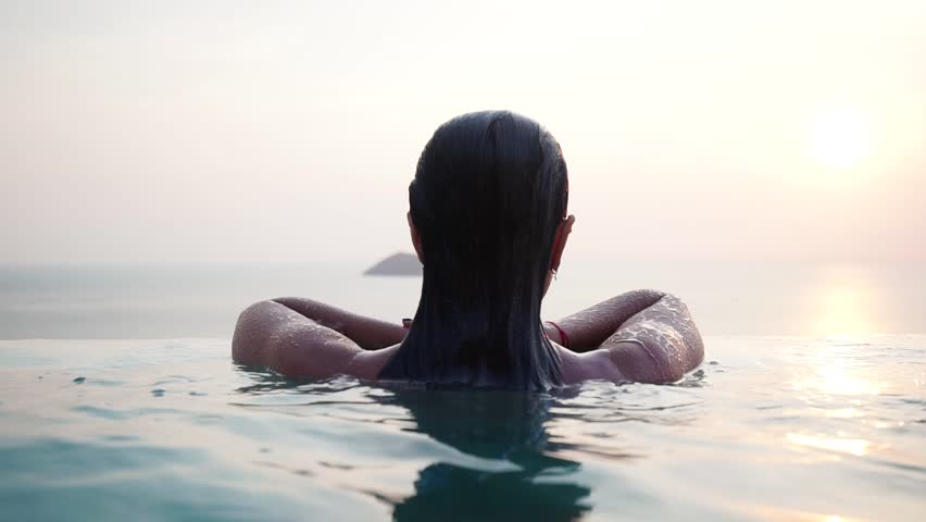 Beautiful attractive girl with sunglasses resting and swimming in a luxury infinity pool with stunning views during sunset. Slow motion | Shutterstock HD Video #1010655140