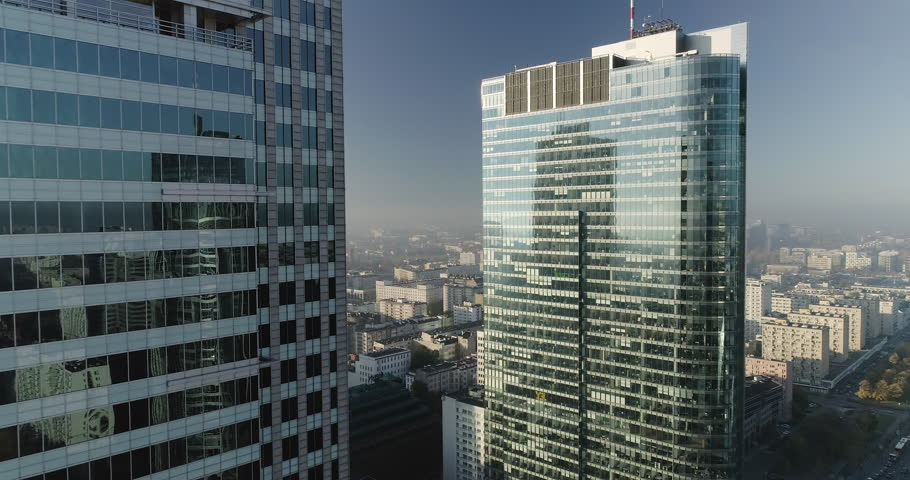 Drone footage in between skyscrapers and glass office buildings in Warsaw city center. Shot is taken during a misty but sunny day in Polish capital city.