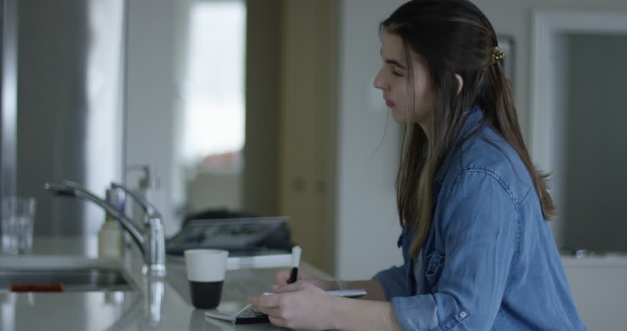 Young woman writing notes on kitchen counter   Shutterstock HD Video #1010688548