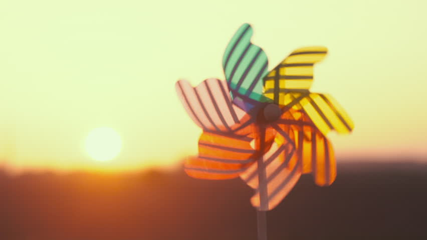Plastic pinwheel rotate color, windmill with blowing a wind against sunset sky of sunny day slow motion. Descending bright disk of sun beyond horizon on field with wheat sun. Nature. Emotions. Relax Royalty-Free Stock Footage #1010698652