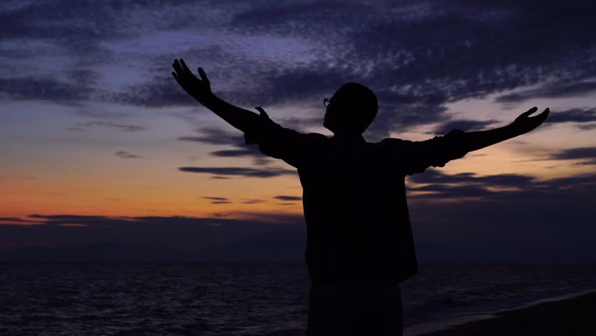 SLOW MOTION: Silhouette of a young man standing at the beach, looking at beautiful sunset, spreading hands and enjoying freedom #1010699204