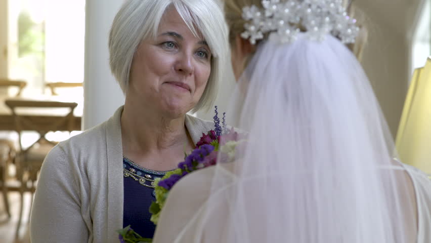 Mother of bride chatting to daughter on wedding day.