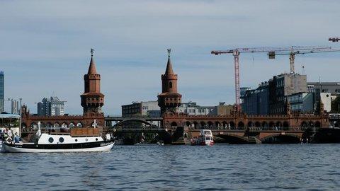 Berlin, Germany - may 2018: Tourist boats on river Spree at Oberbaum Bridge (Oberbaumbruecke) in Berlin, Germany