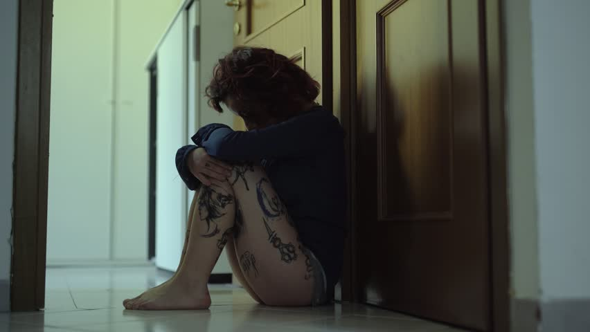 Domestic Violence:Depressed and scared woman sitting in ground in the dark | Shutterstock HD Video #1010712782