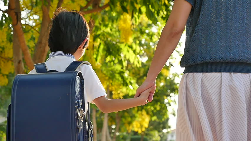 Asian mother holding hand of little son with backpack outdoors, back to school slow motion   Shutterstock HD Video #1010717768