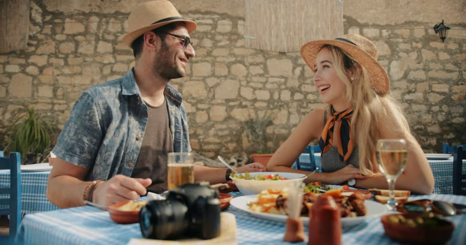 Happy couple on summer holidays in Europe having Mediterranean food at traditional restaurant