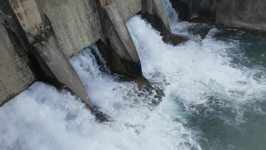Spring flood water flowing on hydroelectric power station dam. | Shutterstock HD Video #1010763638
