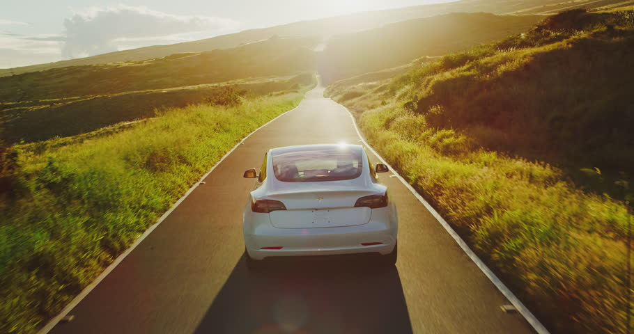 CALIFORNIA, USA - CIRCA APRIL 2018: The much anticipated Tesla Model 3 electric vehicle driving on country road at sunset.