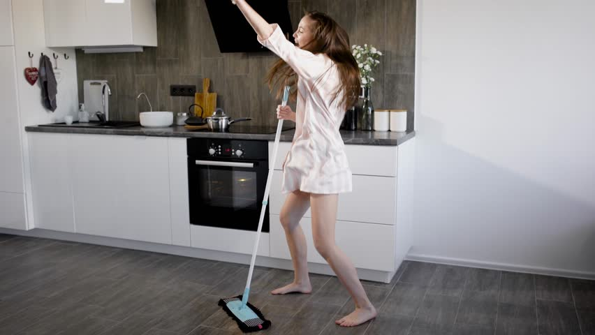 funny girl is having fun, when doing house cleaning, dancing extravagantly around broom in kitchen #1010768564