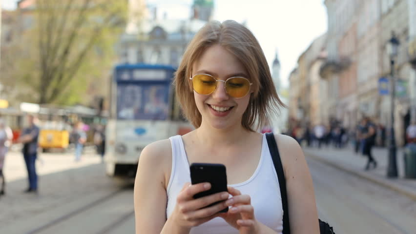 portrait of walking relaxed smiling girl using digital smartphone mobile outdoors blurred tramway on background internet connecting city space 3G traffic app comfortable lifestyle casual clothes Royalty-Free Stock Footage #1010790947