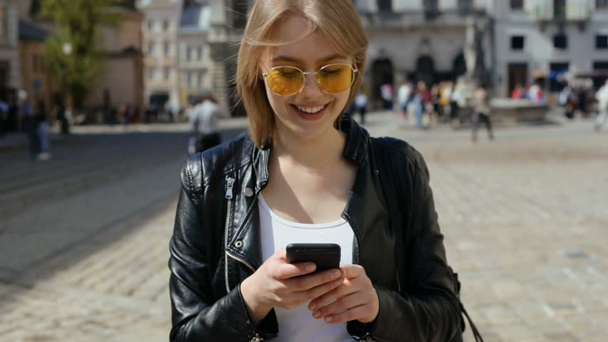 portrait of beautiful young female person going on street holding digital smart phone mobile smiling looking at display internet surfing communication online student girl blog app ebusiness fashion #1010790977