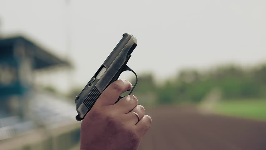 Slow motion close-up starting pistol (gun) in hand makes shot to start track (give signal) and field races at stadium by someone
