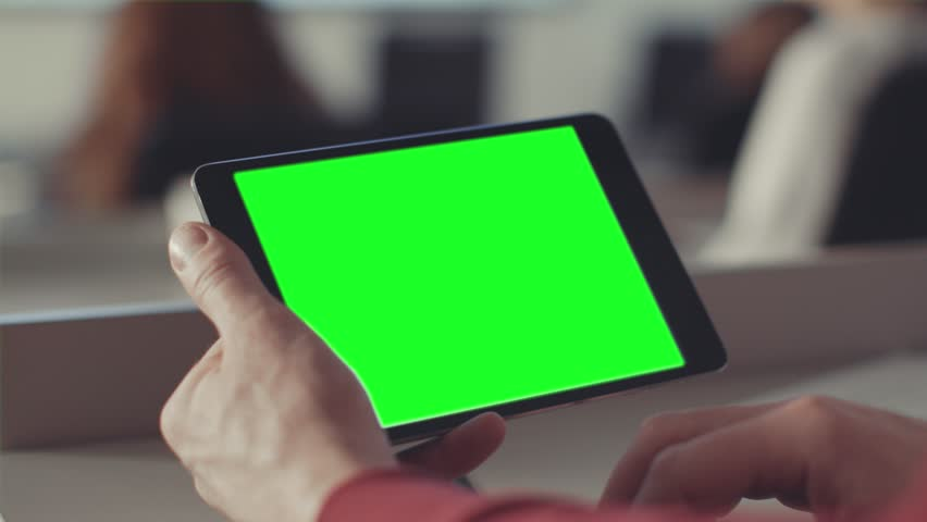 Man looks at the screen of the tablet with a green screen. Stock. Chroma key on the screen of the tablet in the hands