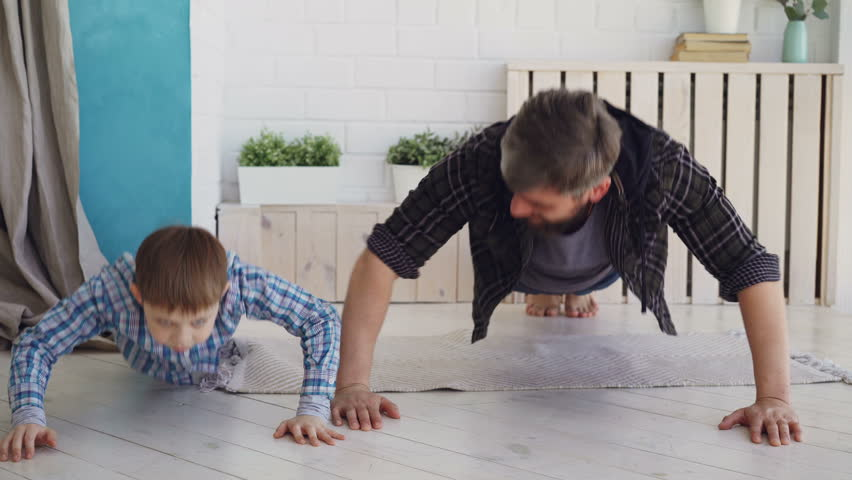 Active handsome father and his joyful son are exercising doing press-up together at home on wooden floor. Happy family, sport and sporty lifestyle concept. #1010801219