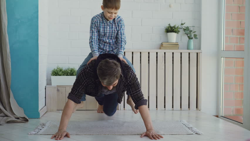 Strong active man is doing push-ups with his laughing little son sitting on his back. Sport, spending time with family, happy childhood concept. #1010801297