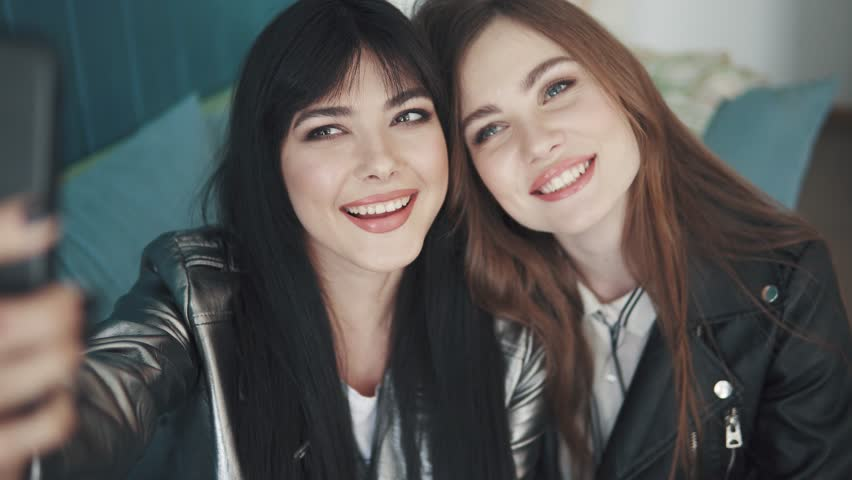 Girlfriends do selfie on mobile phone cameras while sitting in a cafe. two attractive girls take pictures on the camera of the smartphone and fool around