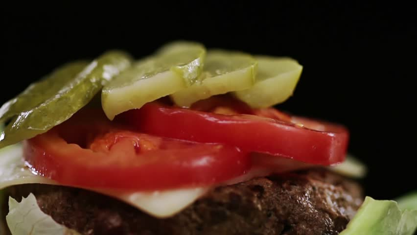 Sliced onions fall on vegetables in a burger. | Shutterstock HD Video #1010815502