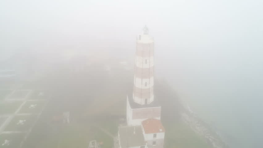 Aerial view of a lighthouse in a misty morning | Shutterstock HD Video #1010819819