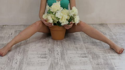 flowers in pot between female legs.