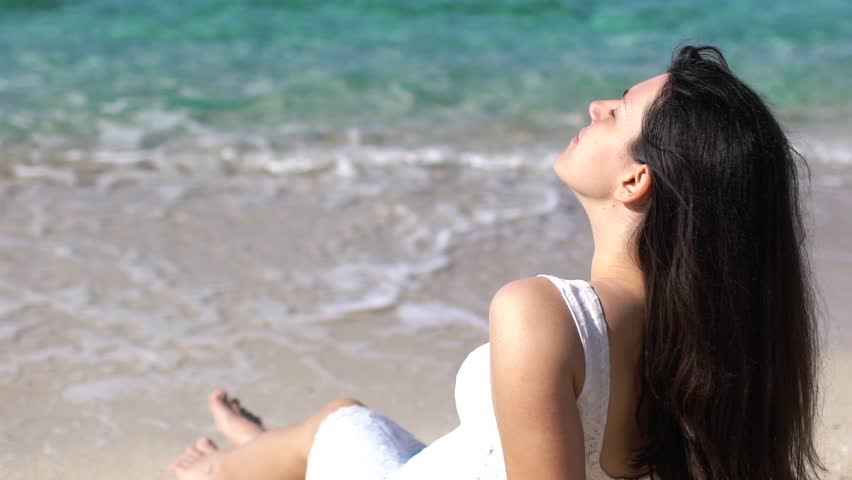 SLOW MOTION: Girl in white dress sitting on a beach. Young brunette woman sitting on a sandy seashore, sunbathing and enjoying. Shot at Thassos island, Greece   Shutterstock HD Video #1010823455
