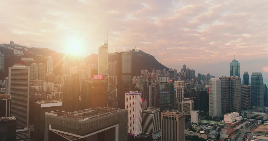 AERIAL. Fast flight between buildings at Hong Kong city centre. Sun light at background.