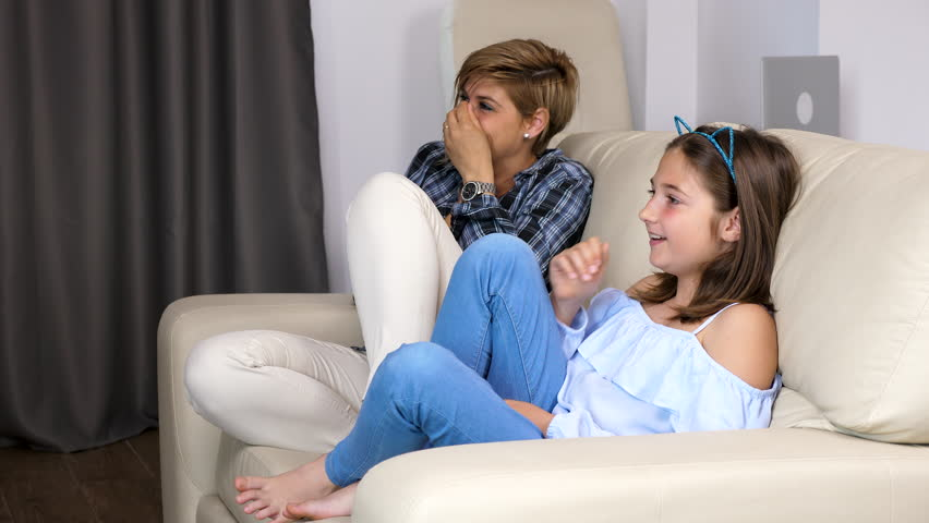 Mother and daughter are having a lot of fun and laughs while watching TV in the living room sitting on the couch. 4k footage. Dolly type shot #1010828171