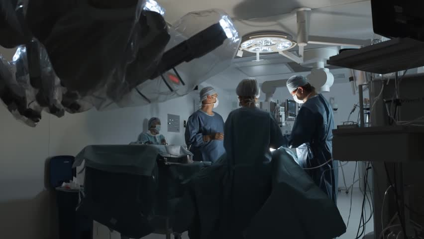 Operating room, team of surgeons prepares patient to cancer removal surgery via Minimally Invasive Robotic Surgery. Hi-tech medical robot, modern medicine, futuristic medical equipment, operation