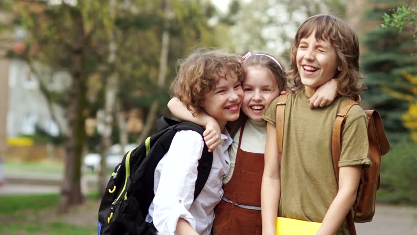 Brothers and sister cheerfully embrace each other on the way to school. Day of knowledge. Back to school. Family education #1010833253