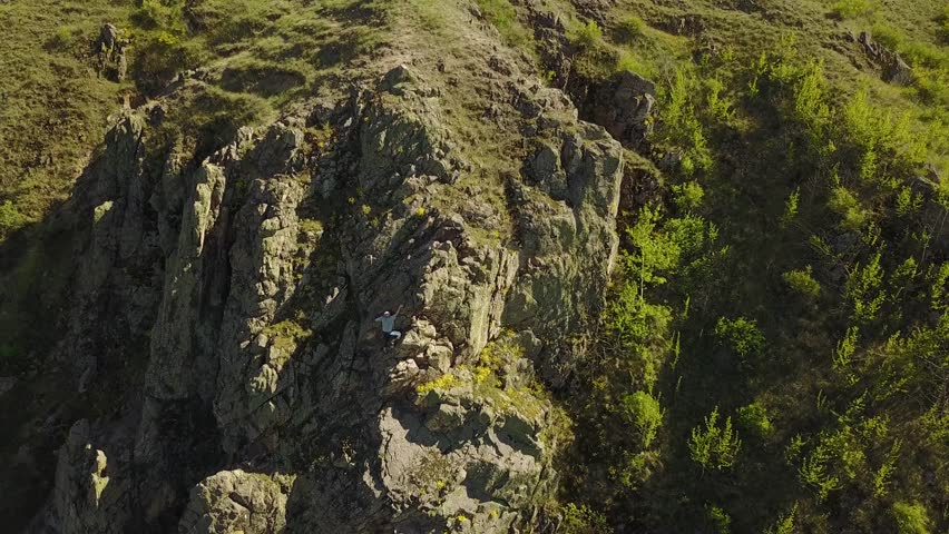 Aerial view of climber solo free climbing on cliffs alone. Man climb the rock without safety harness and ropes. Male climbed the top of mountain and waving hand to camera. | Shutterstock HD Video #1010834726