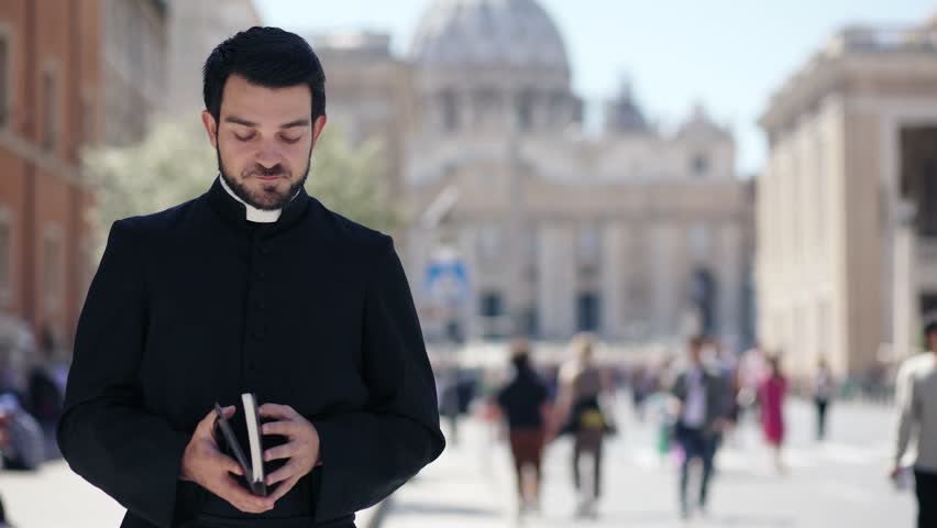 Portrait of bearded Catholic priest scrolls the Bible and smiles at the camera #1010837735