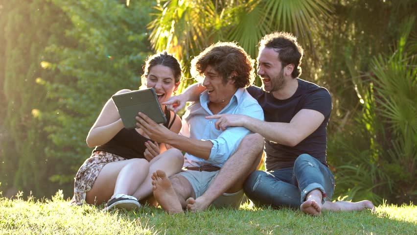 Happy group of friends Are Laughing looking Tablet : summer,joy carefree | Shutterstock HD Video #1010838134