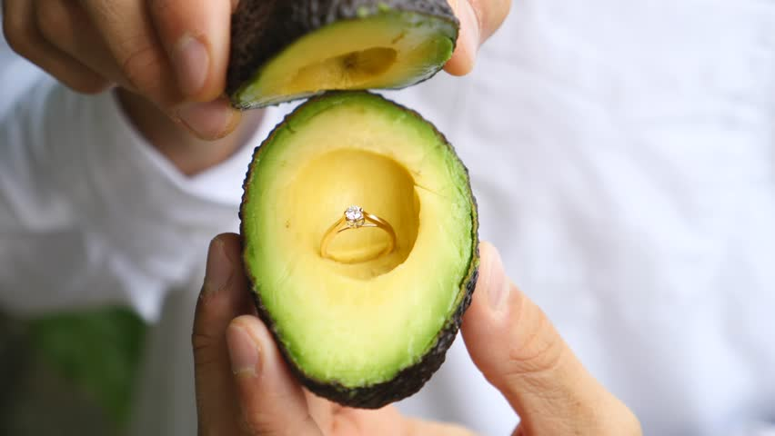 Man Holding Avocado With Engagement Ring to Propose Marriage