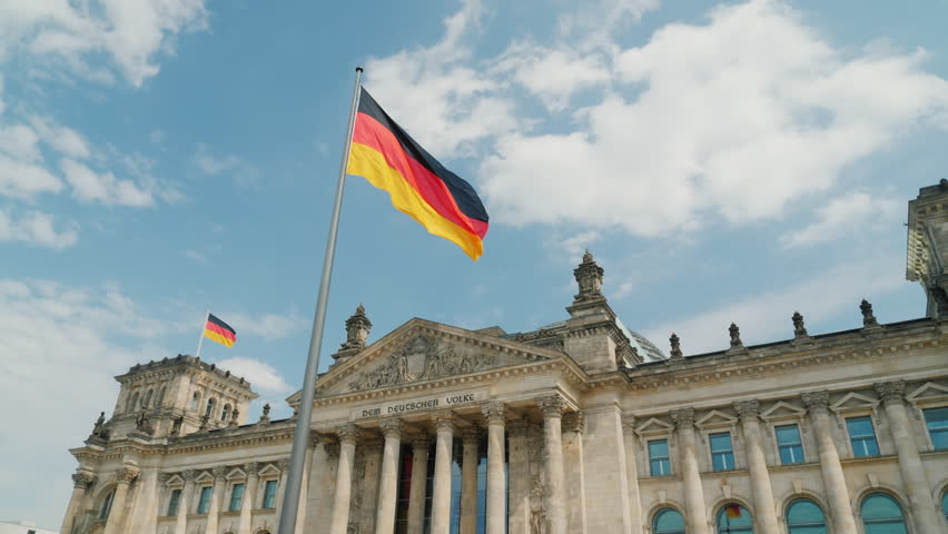 Flag of Germany fluttering in the wind against the backdrop of the Reichstag in Berlin
