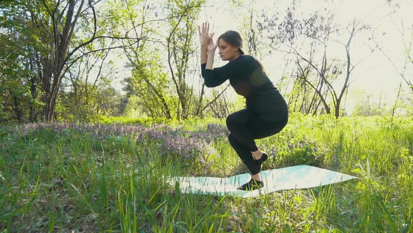 Young pregnant woman doing yoga outside.   Shutterstock HD Video #1010850335
