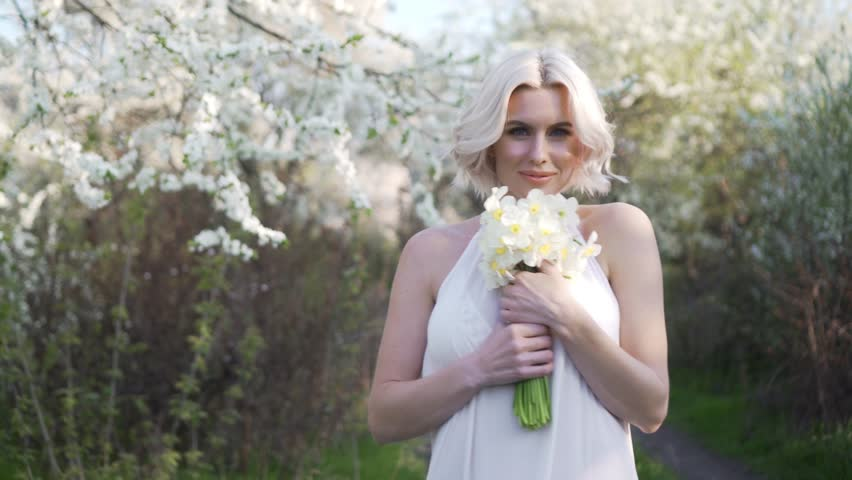blonde girl walking on a blooming garden and resting