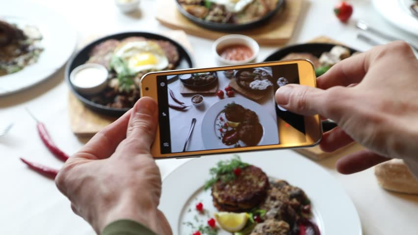 Hands taking photo various dishes with smartphone #1010886995