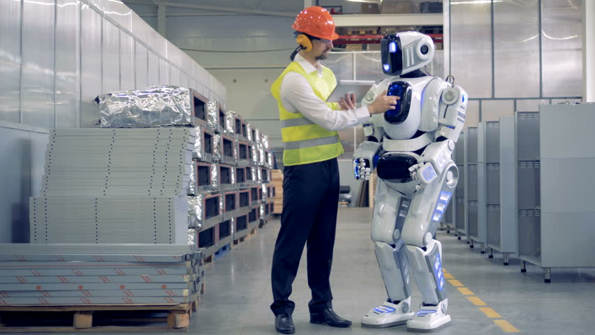 Factory employee and a humanoid are communicating in a factory facility. | Shutterstock HD Video #1010890721
