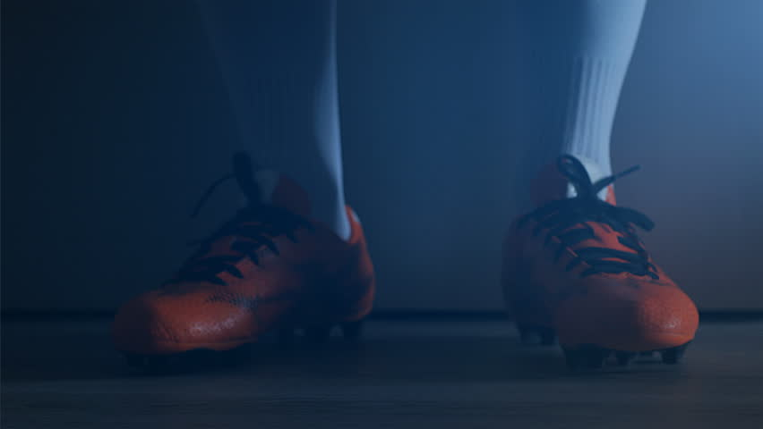 Detail of Soccer football player legs untie shoes after match, 4k, slow motion